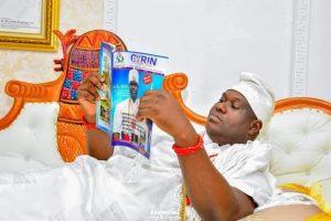 Ooni Ogunwusi reading the magazine after unveiling it
